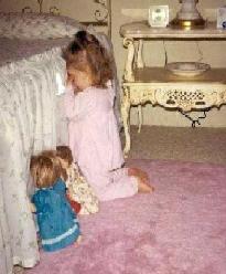 Girl praying with doll.